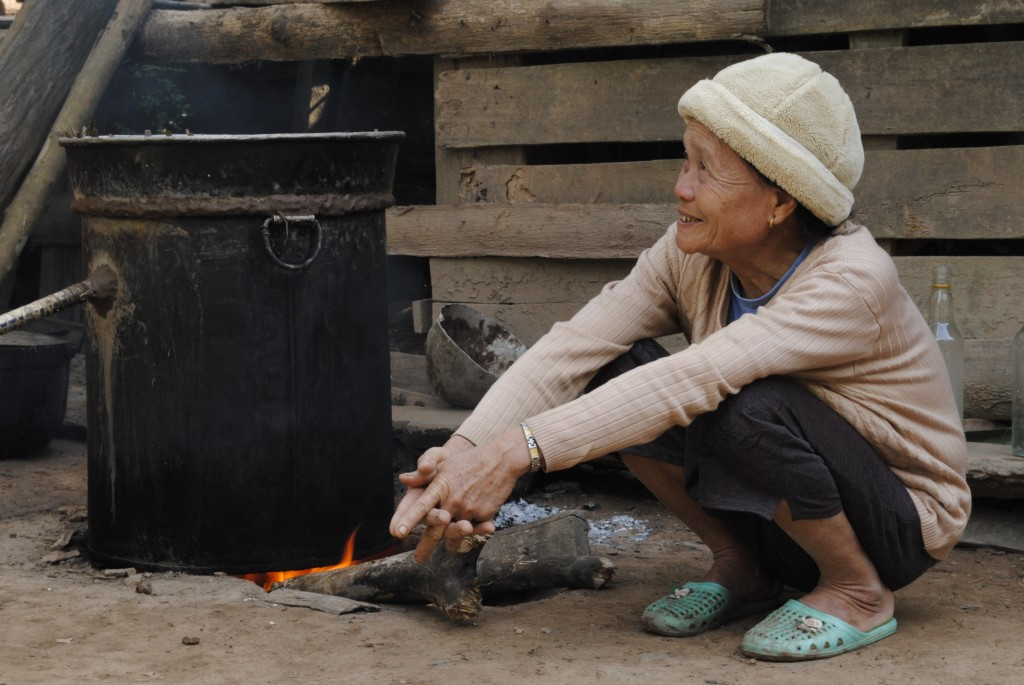 Laos hill tribe woman making Lao Lao (moonshine or rice whiskey)