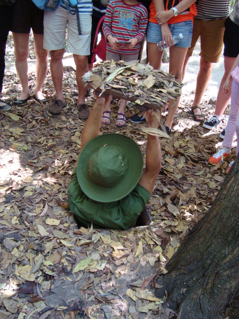 A guide at Cu Chi tunnels showing the size of the actual ones used during the Vietnam War.