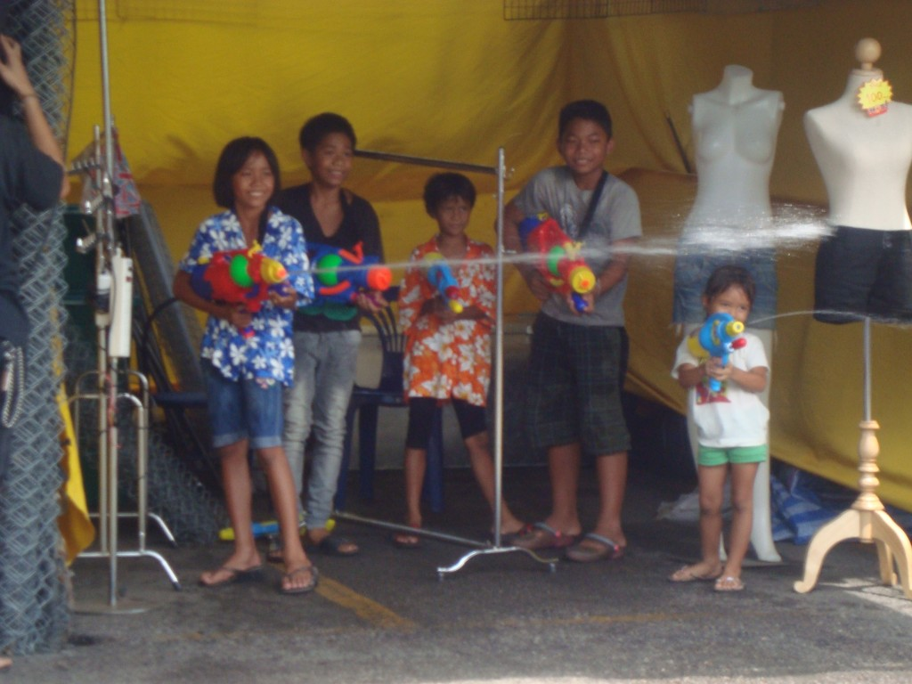 These kids are hiding out in a closed-for-the-day clothing stall and are firing straight at John!